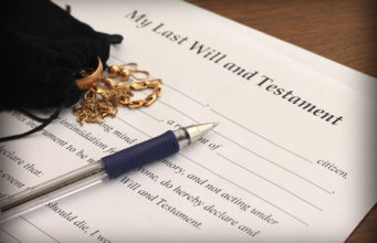 Last Will and Testament form with gold jewelry, close-up