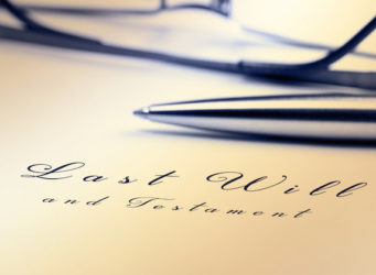 Last will and testament with pen and reading glasses.