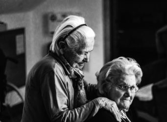 old woman sitting and comforting each other