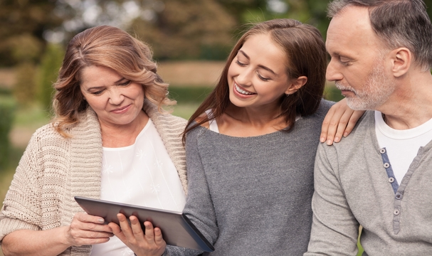 Photo of family viewing a tablet